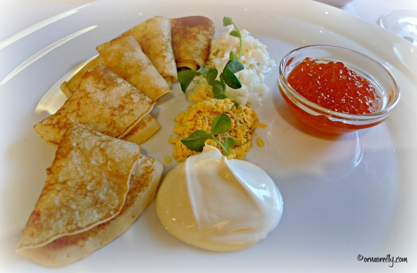Blinis with salmon caviar, hard-boiled egg and sour cream